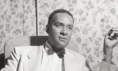 1950:  American writer Richard Wright (1908 - 1960) holds a cigarette while sitting in his hotel room during the Venice Film Festival, Venice, Italy. Wright had attended the screening of director Pierre Chenal's film, 'Native Son,' which was adapted from his novel and starred the author. He is wearing a pale-colored suit and a bow tie.  (Photo by Hulton Archive/Getty Images)